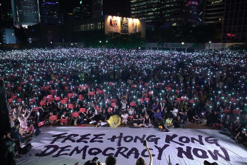 People in Hong Kong manifestates for more Democracy. A banner on the floor states: Free Hong Kong. Democracy now.
