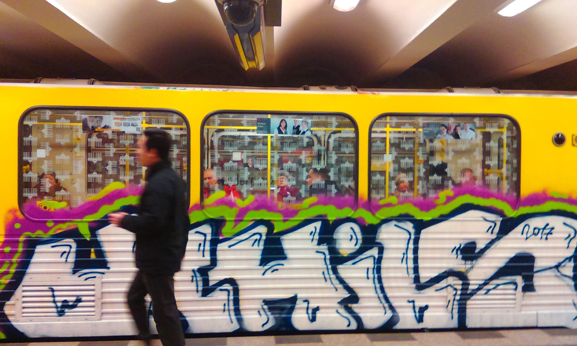 A person walks by the UCHILS Graffiti Bombing on the yellow panel of the Berlin Metro.