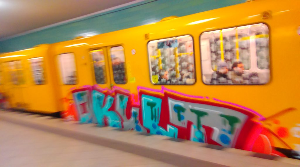 The OKULT Graffiti leaves with the subway. Letters in Blue and grey Fill Ins and red Outlines.