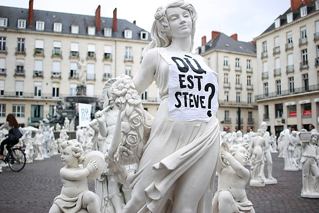 The sculpture of a woman wears a white fabric cover on which it says printed: Where is Steve?
