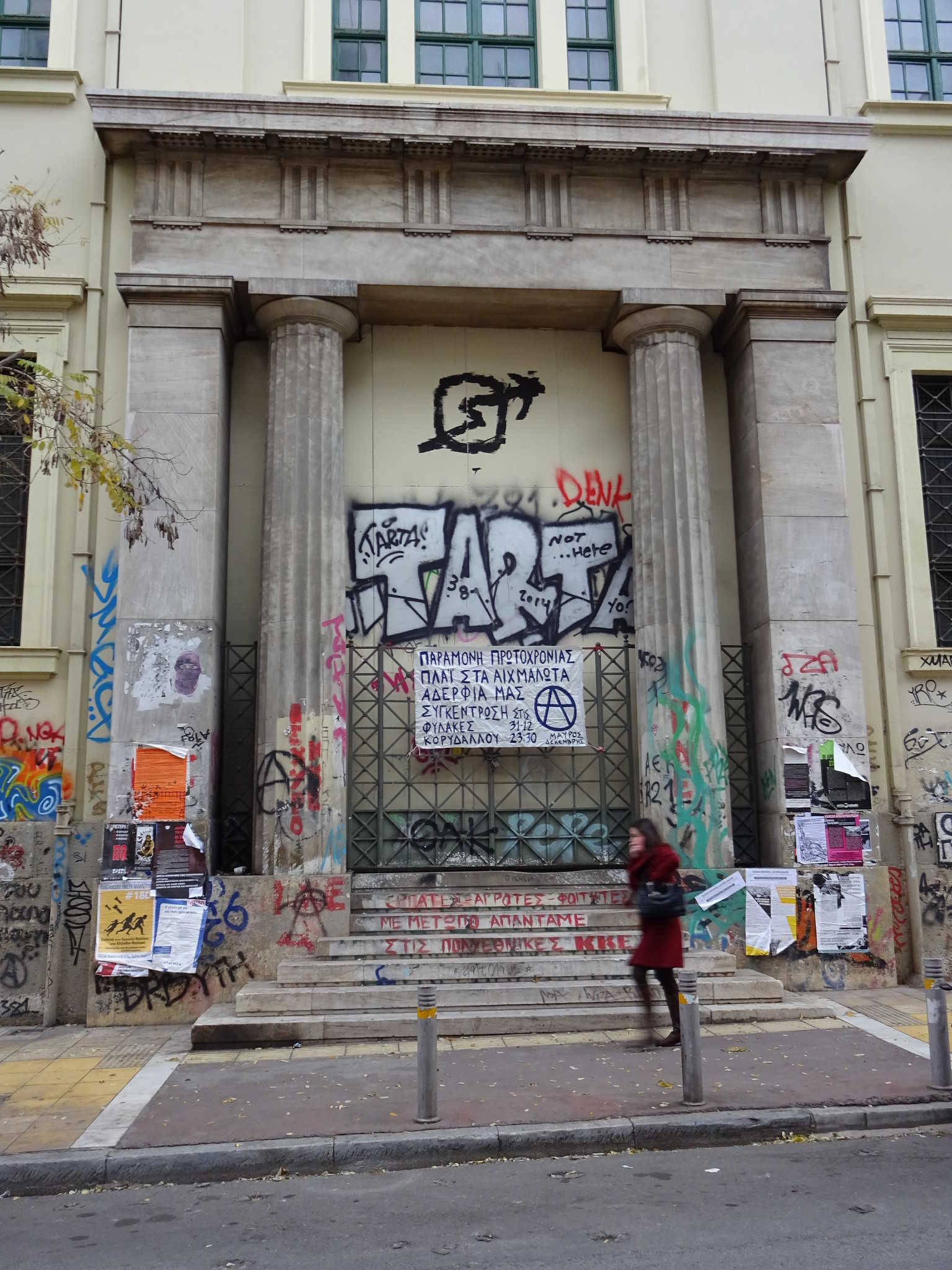 Image of a front door of the polytechnical Univserity in Athen, Exarchia. On the upper side oyu can see the sign of the political squat movement: A circle with an arrow crossing trough. A person is walking by the steps leading to the door.