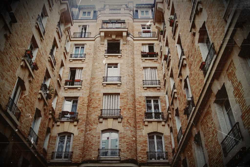 "Caption of a courtyard in the neighboorhood of ""Batignolles"" in the 17th Arrondissement. The building is made of orange bricks and is quite dense. More then 6 storeys high the three buildings are filling the entire image."