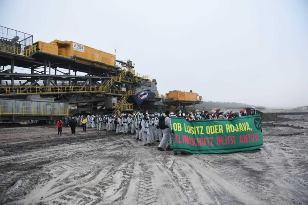 """Klima-Aktivisten mit weißen Maleranzügen und einem Transparent mit der Aufschrift: """"Ob Lausitz oder Rojava, Klimaschutz heißt Antifa!"""" in der Tagebaugrube."""