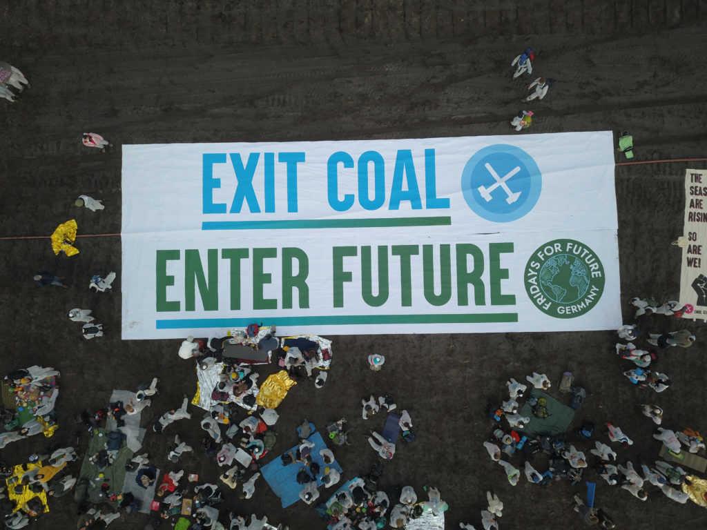 """""""EXIT COAL - ENTER FUTURE"""" steht auf einem ausgerollten Transparent der Klima-Aktivisten."""