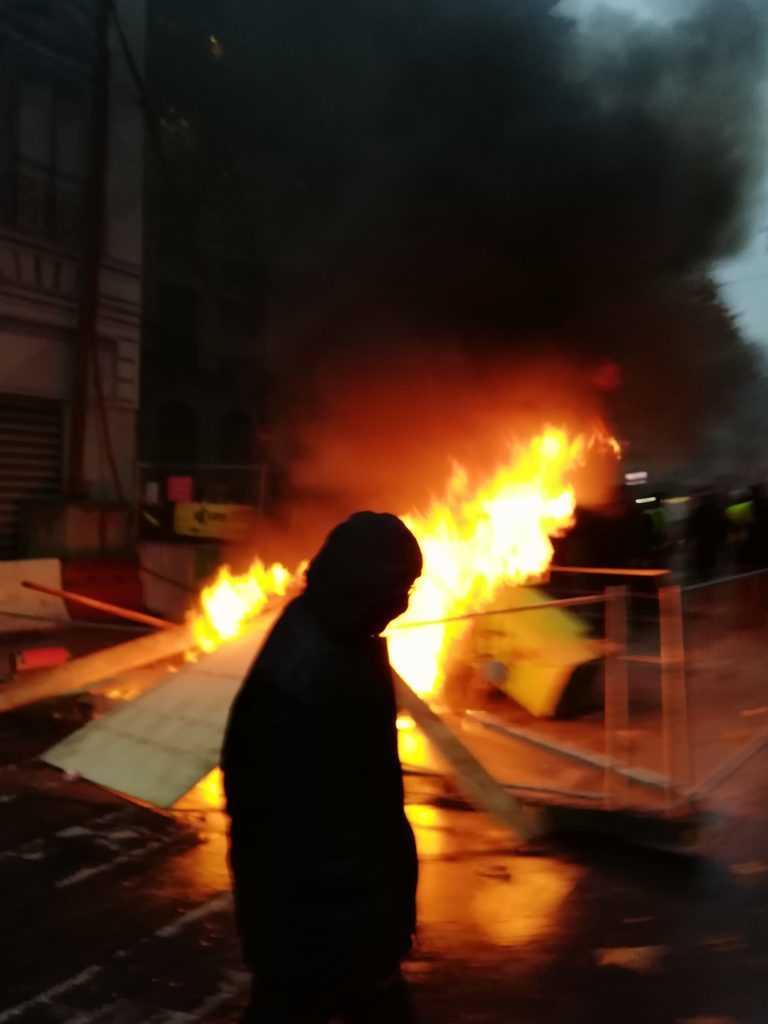 Erste 1. Dezember 2018 Gilets Jaunes Bewegung in Paris. Eine schwarze Silhoeutte steht vor einer brennenden Barrikade. Urbanauth 2018