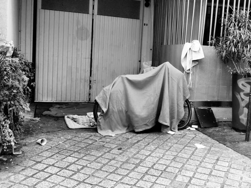 Avec une couverture au dessus d'un vélo, la personne se abrite dans une entrée de garage, 9ème Arrondissement de la capitale françaises.