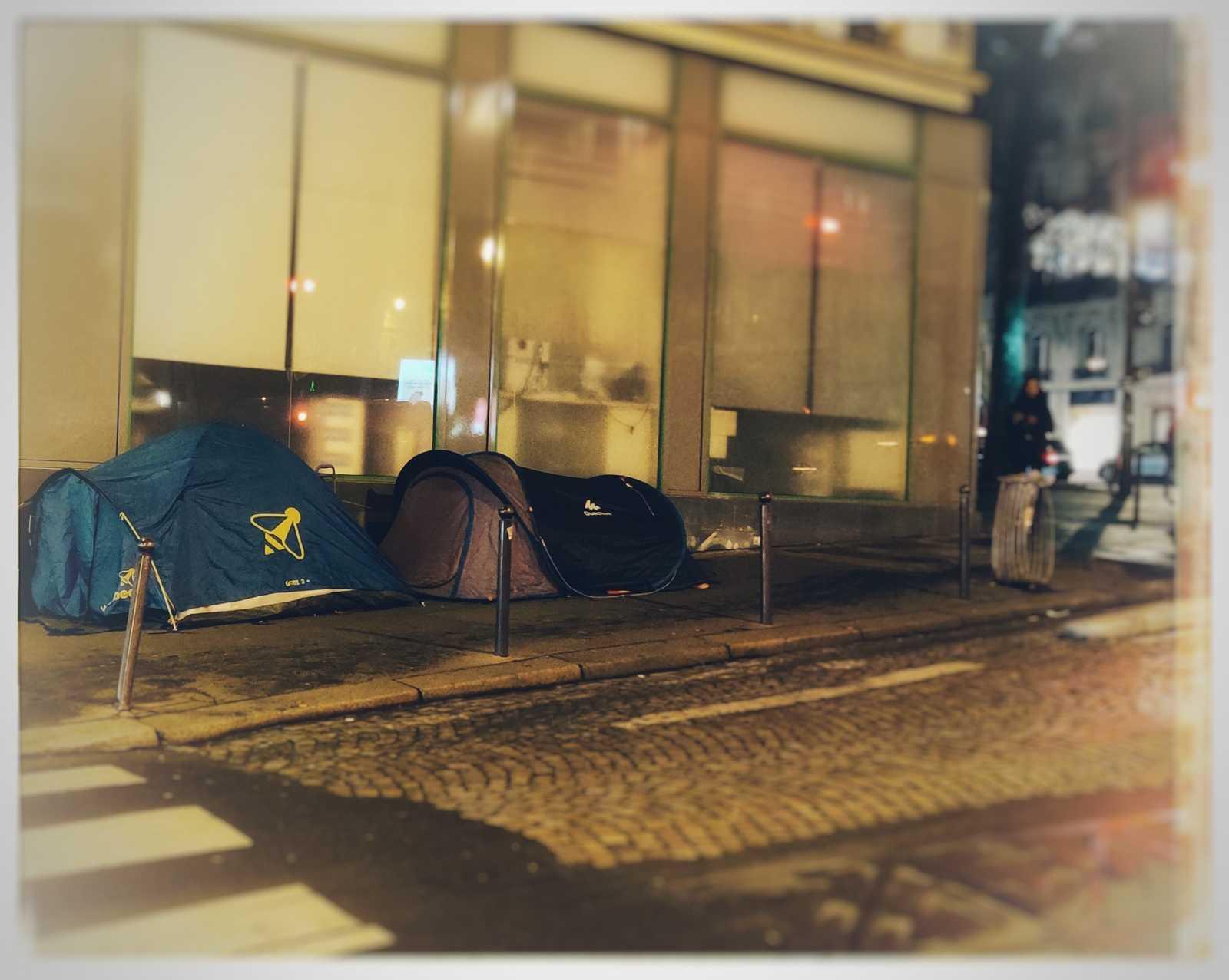 Die Autofahrbahn besteht aus Pflastersteinen, während das an die Zelte angrenzende Gebäude eine glatte Marmorfassade aufweicht. Das Bild wurde bearbeitet sodass der Licht und Schärfe Fokus auf die Zelte liegt. Die restlichen Farben, darunter das rot einer Ampel, werden verschwommen dargestellt. Das Photo wurde von Urbanauth 2020 in Paris aufgenommen.