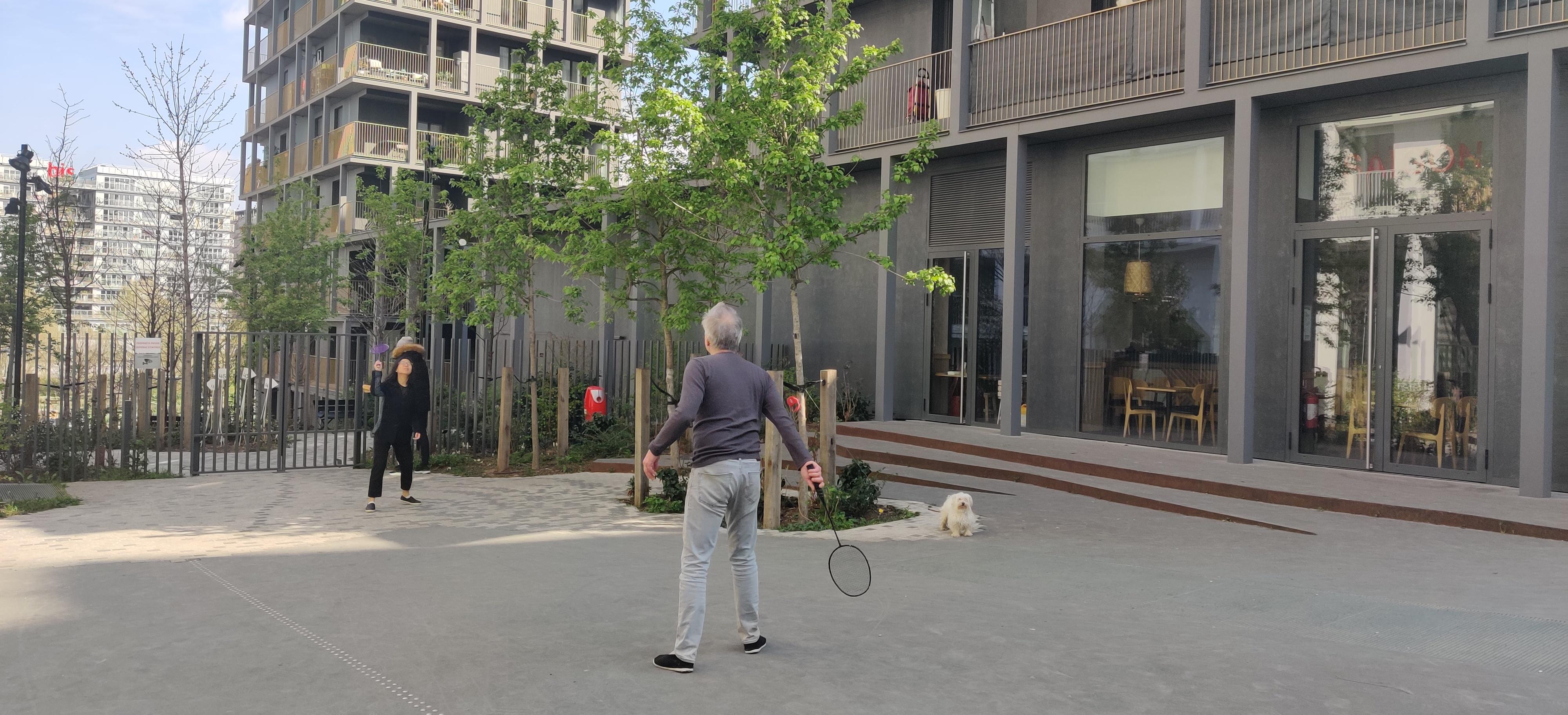 écoquartier clichy batignolles paris, des habitants jouent devant l'immeuble, automne, un passant passé, l'environnement est propre