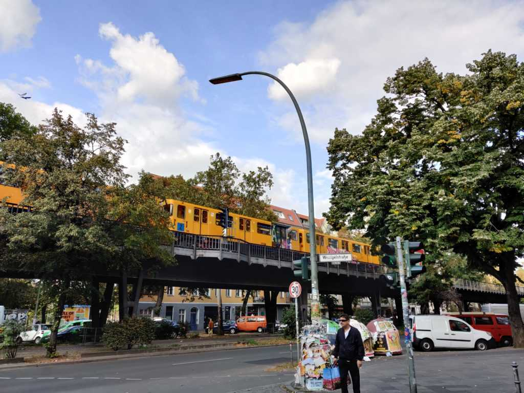 The yellow subway of the BVG is crossing by on a surelevation. Below, a man stands waiting at the street. The image was taken near Berlin / Wrangelkiez