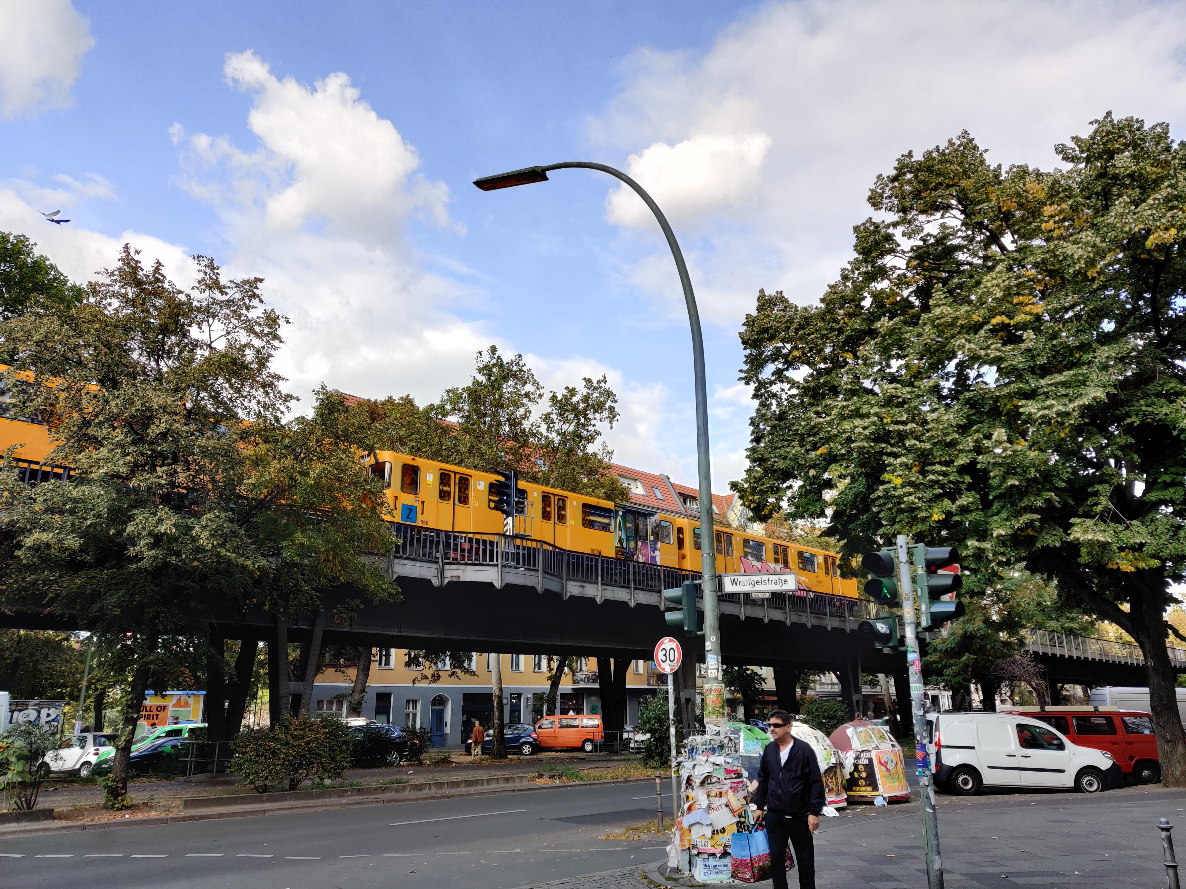 train jaune BVG passant sur un pont. Homme attends rue. Été, ciel bleu, un peu de nuages. Berlin Wrangelkiez Germany