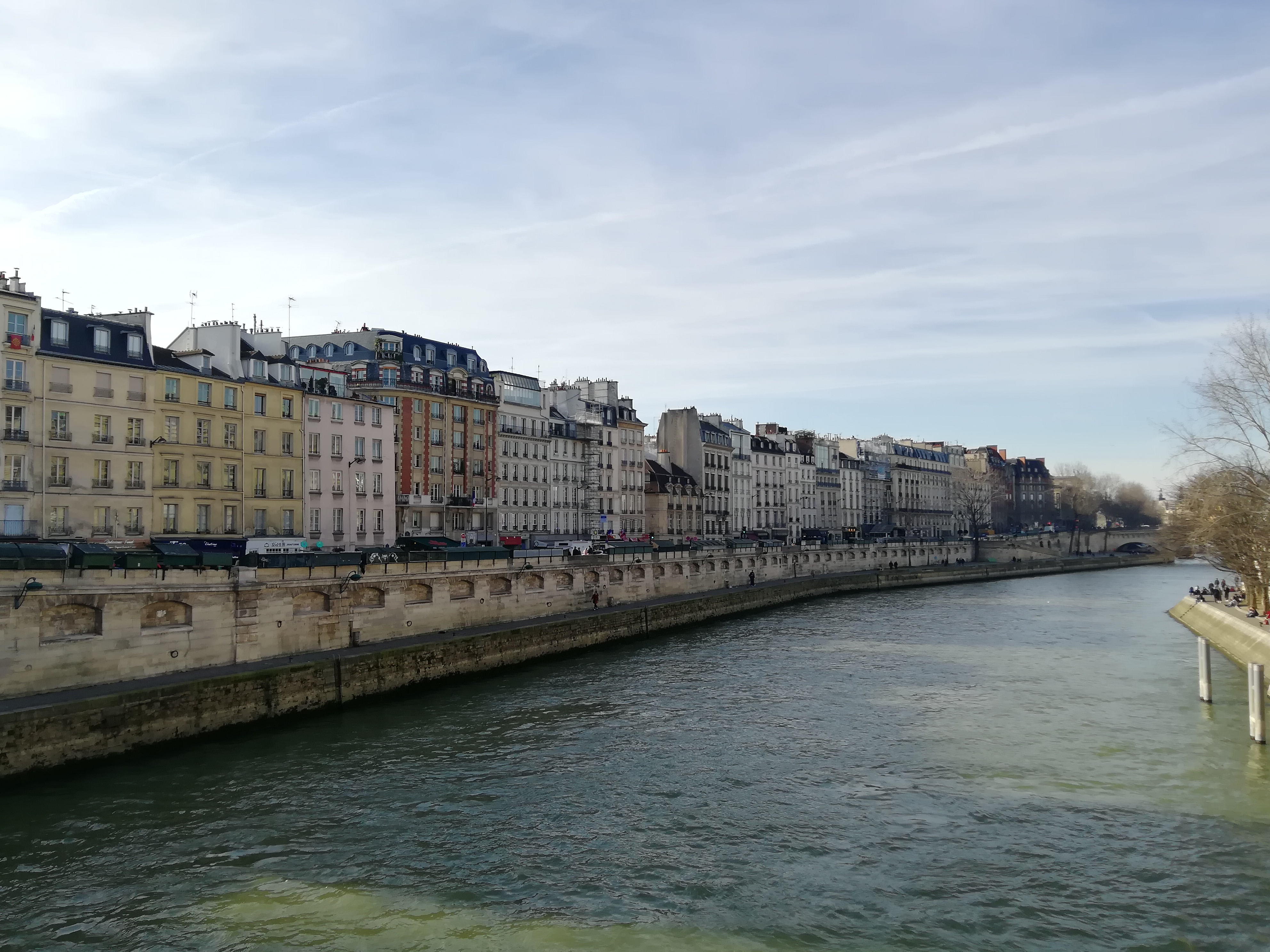 Fluss Seine Paris Frankreich, Flusswehr mit Haussmannischen Fassaden, Herbstwetter ohne Wolken, Wasserfarbe grün bis dunkelgrün bei Schatten.