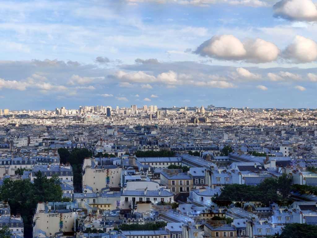 Stadtlandschaft von Paris, grau-silberne Häuserdächer, bewäktes Wetter, endlose Urbanisierung bis zum Horizont